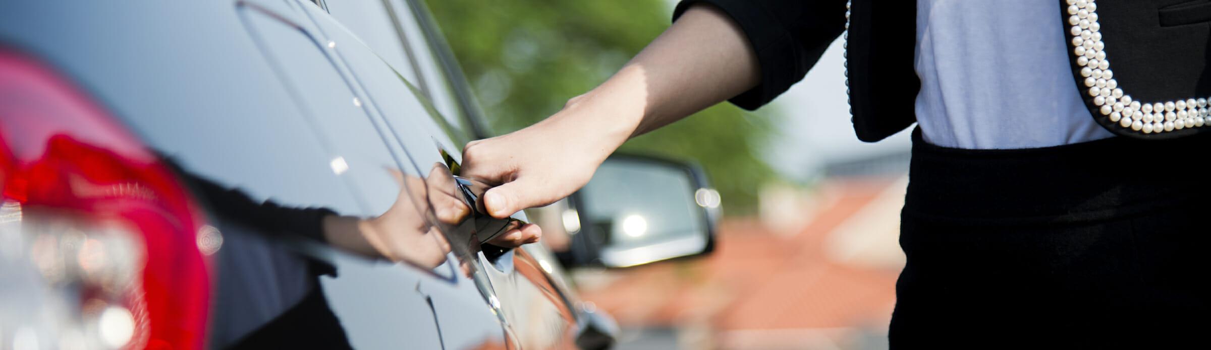 Closeup of a businesswoman opening a car door.